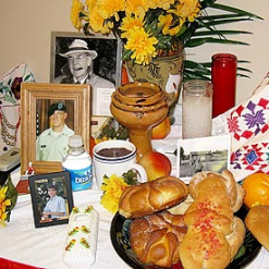 The centerpiece of the exhibit is a traditional ofrenda, an altar with food and beverage offerings, as well as flowers and photos of deceased family members.