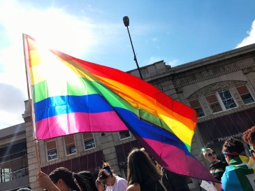 Salem students walk in Pride parade carrying flag; Photo by Kadia King